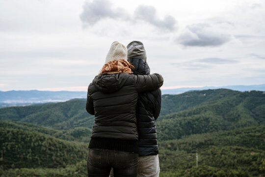 Couple embracing while looking at mountains against sky during winter