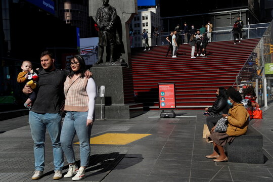 A couple poses with a baby in front of the red steps of the Times Square ticket booth during the coronavirus pandemic in New York City