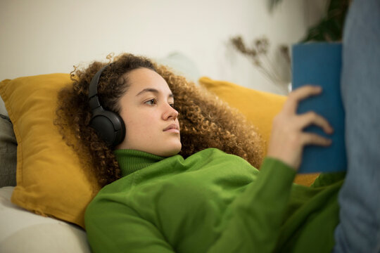 Young woman with book lying on bed while listening music through headphones at home