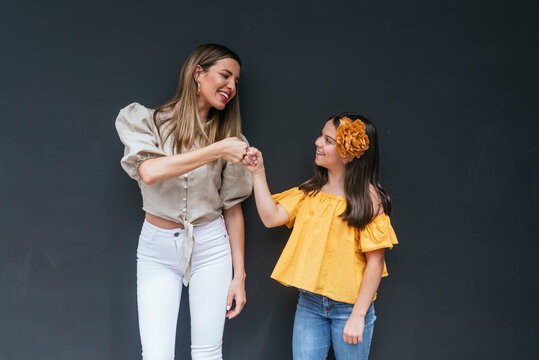 Cheerful mother and daughter giving fist bump while standing against black background