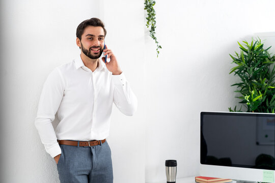 Male professional with hands in pockets on phone call standing against white wall at work place