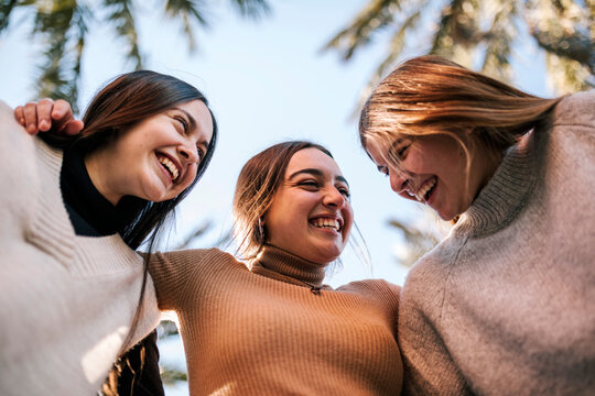 Cheerful female friends huddling against clear sky in park