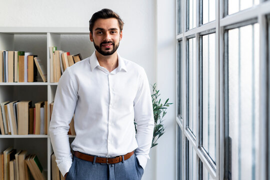 Smiling businessman with hands in pockets standing against bookshelf in office