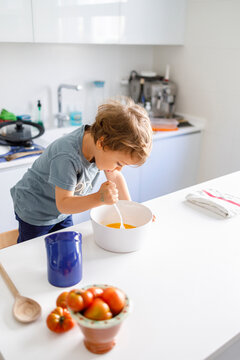Little boy cooking in kitchen at home
