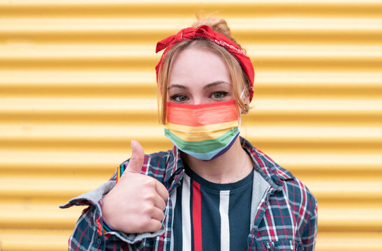 Young woman wearing multi colored face mask gesturing thumbs up while standing against yellow wall