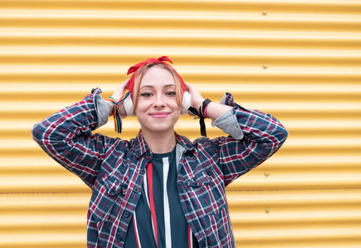 Woman wearing headphones smiling while standing against yellow wall