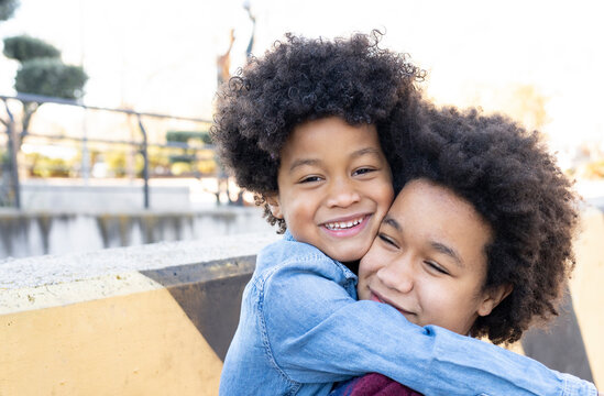 Smiling sibling embracing each other while standing at park