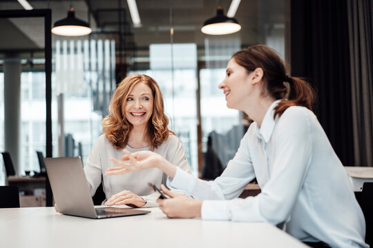 Businesswoman laughing while discussing with female colleague during meeting in board room