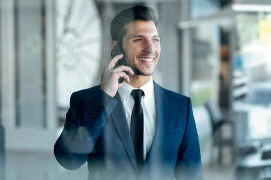 Entrepreneur smiling while talking on mobile phone standing at office