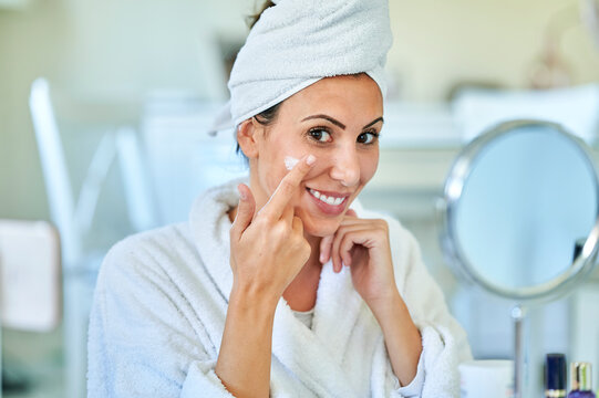 Smiling woman applying cream on her face at home