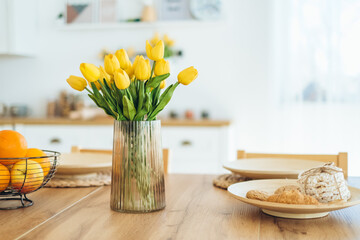 Obraz Yellow tulips in a vase on the table. Spring holiday, Easter, home decor. - fototapety do salonu