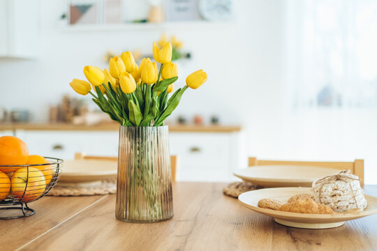 Yellow tulips in a vase on the table. Spring holiday, Easter, home decor.
