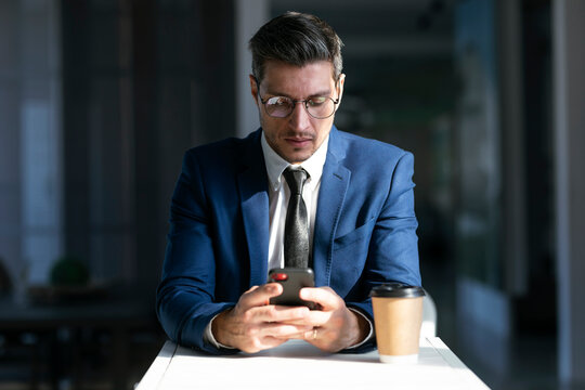 Entrepreneur wearing eyeglasses using mobile phone while sitting in cafeteria at office
