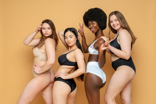 Confident young women in lingerie standing against yellow background