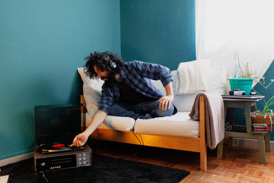 Hipster man with headphones adjusting disk of turntable while sitting on sofa in living room