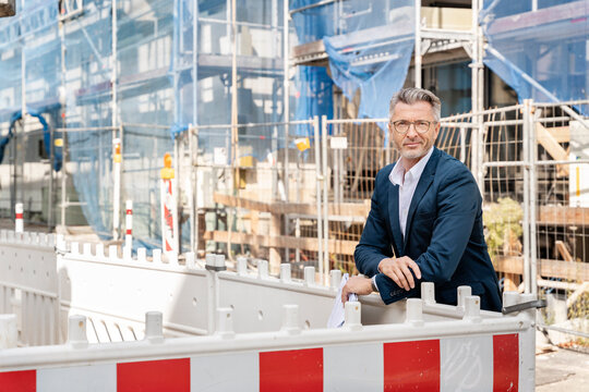 Mature entrepreneur wearing eyeglasses smiling while standing at construction site
