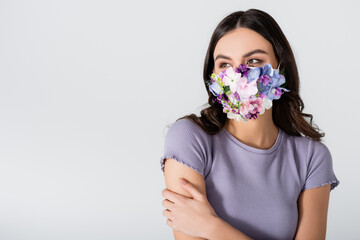 young woman in medical mask with flowers isolated on white Fototapete