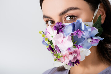 young woman in medical mask with blooming flowers isolated on white Fototapete