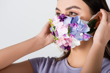 young woman wearing medical mask with blooming flowers isolated on white Fototapete