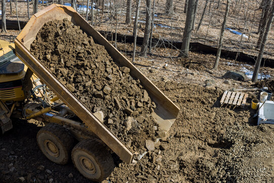 A large track articulating dump truck unloading of rock and soil at a new road project