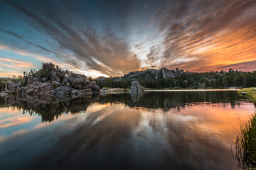 dramatic summer sunrise with the sky and clouds reflecting on the still Sylvan Lake in the Black Hills of South Dakota.