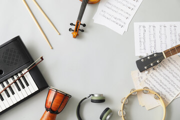 Frame made of different musical instruments and music notes on light background
