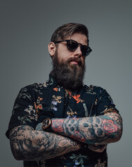 Portrait of a brutal man with sunglasses wearing stylish clothing with watch in gray background....