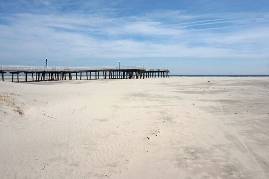 Pier on Sand with Ocean on Sunny Day