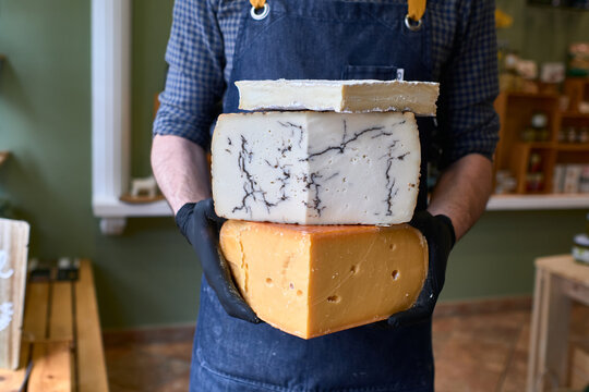 Portrait of a handsome cheese vendor in uniform holding three large cheeses in front of the store.