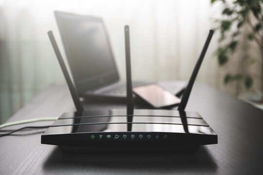 WIFI router connected to the internet on table and laptop in the background