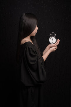 It is time to wake -up; conceptual classic portrait of a girl en profile in black holding a clock; five before twelve o'clock
