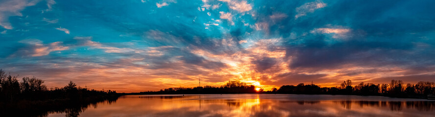 High resolution stitched panorama of a beautiful autumn or indian summer sunset with reflections...