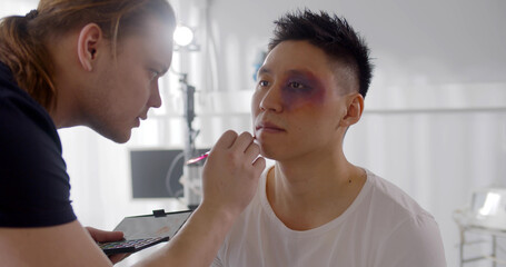 Obraz Male visagiste applying bruise makeup on face of young man before shooting scene - fototapety do salonu