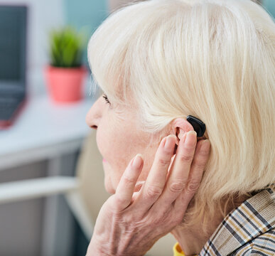 Senior woman with hearing aid behind the ear listens to ambient sounds. Hearing loss treatment concept at older people