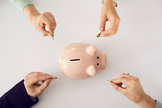 Hands putting money in pink piggy bank on white table background. People saving up together, family household income, opening account, banking, joint venture, economy concept. High angle, from above