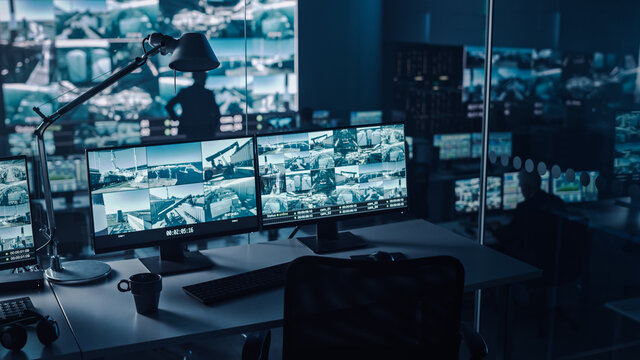 Two Digital Computer Screens with Surveillance CCTV Video in a Harbour Monitoring Center with Multiple Cameras on a Big Digital Screen. Employees Sit in Front of Displays with Big Data