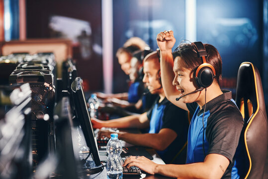 Side view of excited young asian guy, male cyber sport gamer looking at PC screen and raising hand up while