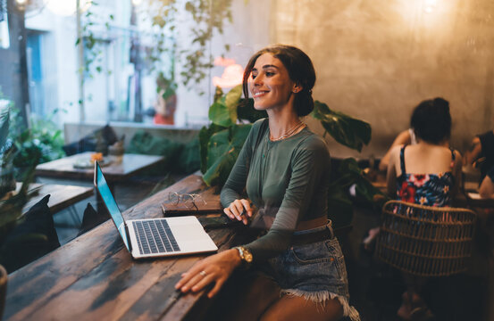 Cheerful woman working on laptop in cafe