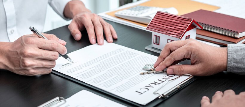 Real estate agent are presenting home loan and giving keys to customer after signing contract to rental house with approved property application insurance form contract