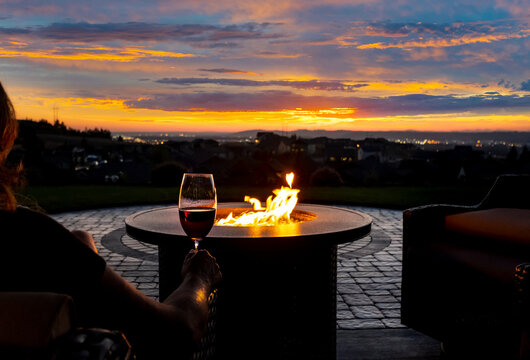 A woman drinks a glass of wine in front of a fire pit on the luxury patio of a hillside home overlooking city lights.