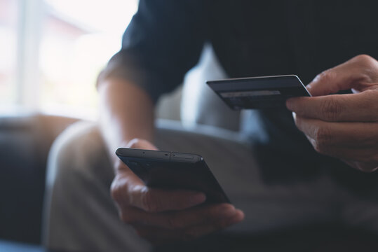 Man using credit card and mobile phone for online shopping and internet payment via mobile banking app
