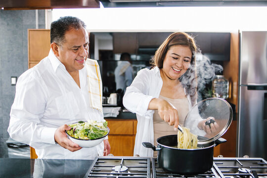 latin couple middle age woman cooking together in home in Mexico city