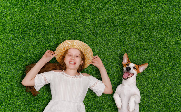 Laughing girl and cute dog enjoy summer day on the grass