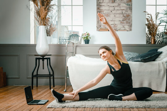 Positive athletic woman with neatly tied hair and tight sportswear stretching   at home. The young woman goes in for sports at home.