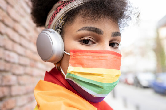 afro woman with gay pride mask and headphones