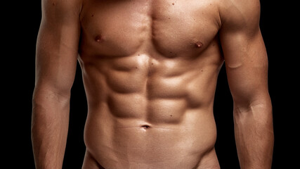 Closeup image of a strong athletic man showing muscular body and sixpack abs isolated black background.