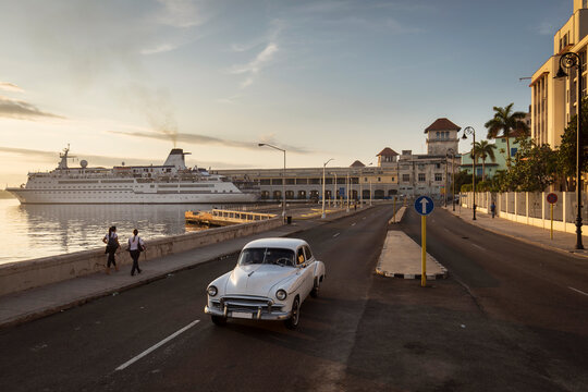 Old car on Malecon street of Havana with sunrise in background. Cuba