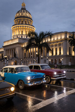 Old car on streets of Havana with Capitolio building in background with reflection on rain time. Cuba