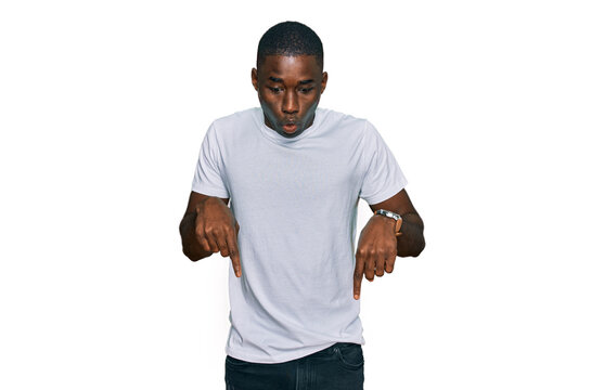 Young african american man wearing casual white t shirt pointing down with fingers showing advertisement, surprised face and open mouth