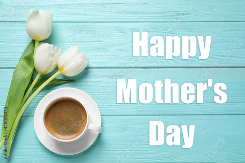 Happy Mother's Day. White tulips and coffee on light blue wooden table, flat lay